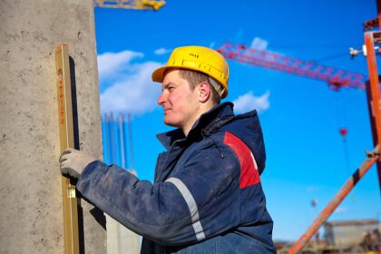 Construction worker checking vertical level of house wall