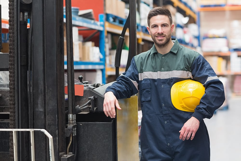 Manual worker leaning against the forklift in warehouse